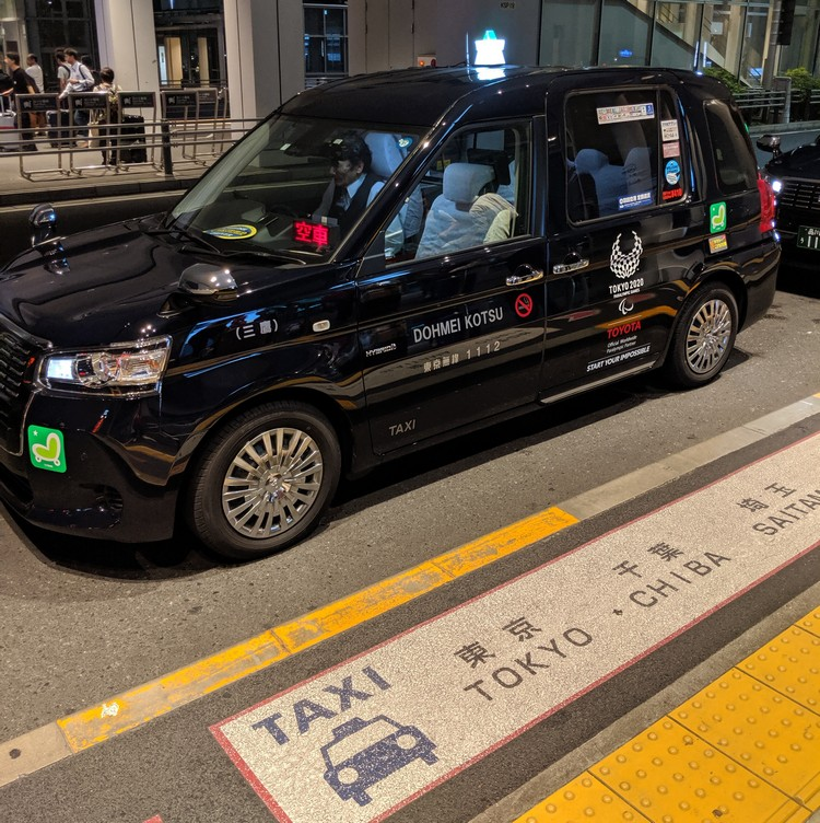 black airport taxi waiting outside at the Tokyo Haneda Airport in Toyko Japan