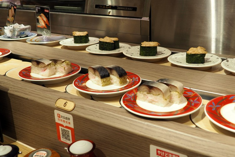 conveyor belt sushi restaurant in Kyoto Japan, nigiri sushi plates pass by the table