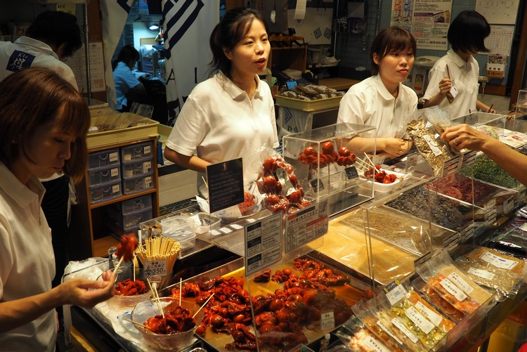 eating red octopus on a stick at Nishiki Market in Kyoto Japan