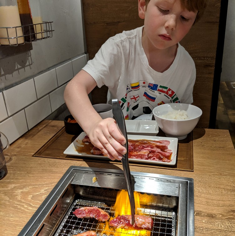 Boy grilling meat on a table inside a Japanese restaurant, Yakiniku Japanese cuisine