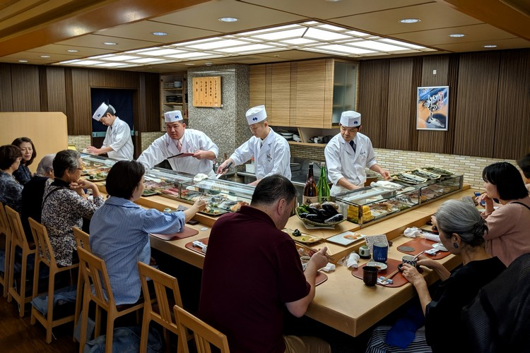 Sushi chefs inside a Japanese restaurant in Tokyo serving sushi and Japanese cuisine