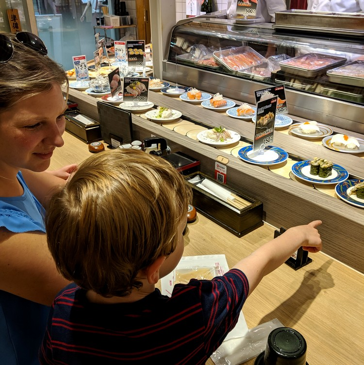 Conveyor belt sushi restaurant in Kyoto tourist area. Beginners Guide to Food in Japan for first time visitors