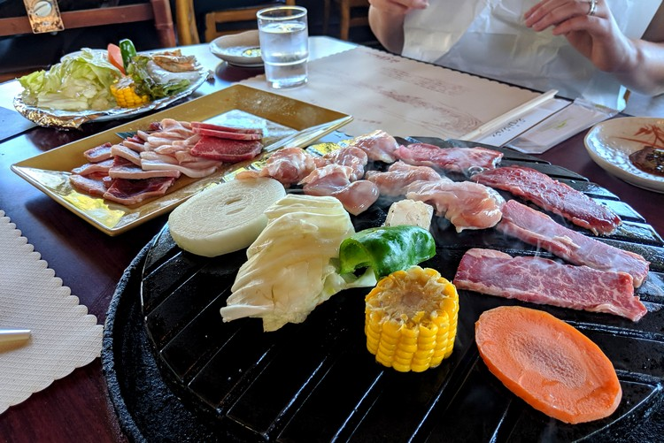 Grilling meat and vegetables at Rokkosan Genghis Khan Palace restaurant on Mount Rokko in Kobe, Japan